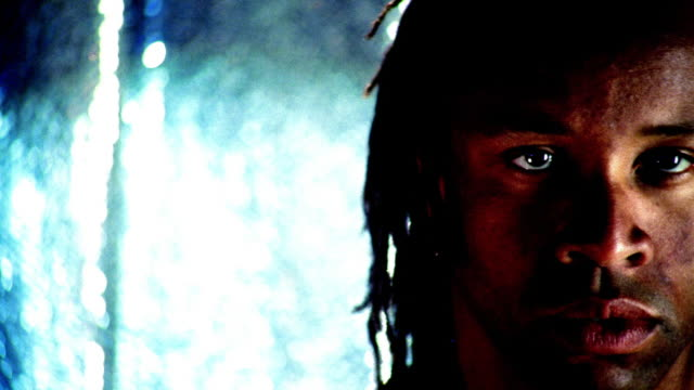 close up tilt down shirtless black man with dreadlocks dancing and closing eyes / light blue sequined background - shirtless stock videos & royalty-free footage