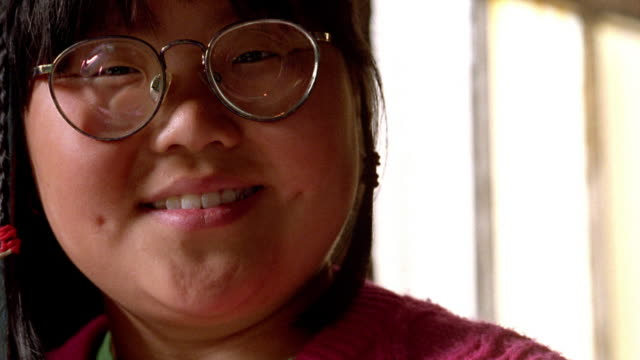 Close up tilt down tilt up Asian girl with eyeglasses looking serious then smiling / Nova Scotia, Canada