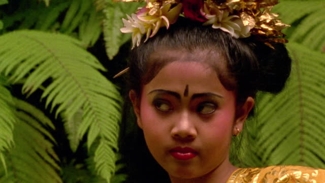 close up tilt down tilt up Balinese girl performing traditional Indonesian dance / Bali, Indonesia