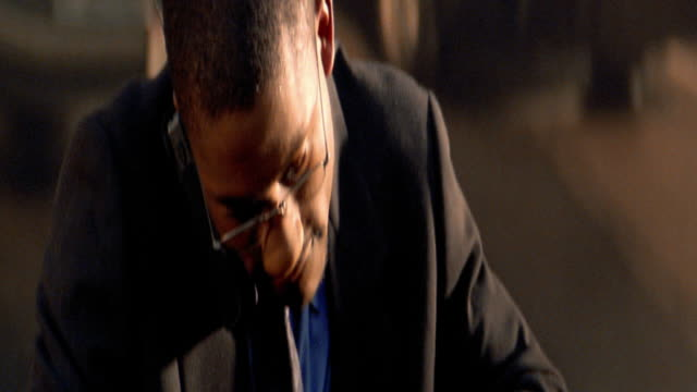 close up tilt down tilt up excited black businessman answering cellular phone and writing in appointment book - answering stock videos & royalty-free footage