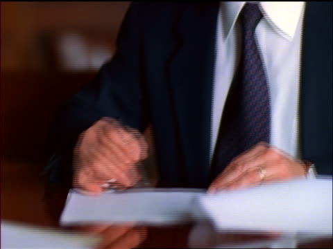close up tilt down + tilt up from hand to face of middle-aged businessman in eyeglasses signing contract at table