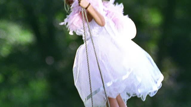 close up tilt down tilt up pan girl in formal dress + wings standing on tree swing outdoors - ängel bildbanksvideor och videomaterial från bakom kulisserna