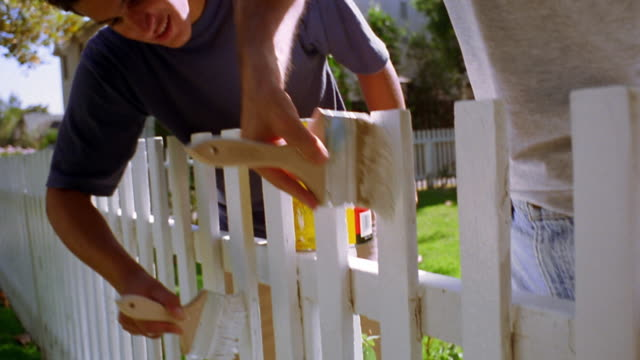 close up tilt down tilt up grey haired man + teenage boy painting white fence in yard - recinzione video stock e b–roll