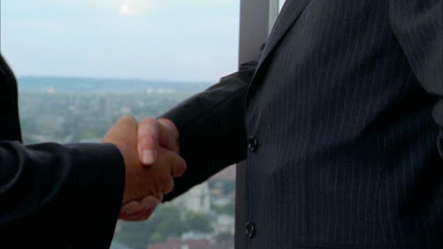 Close up tilt down tilt up two businessmen smiling and shaking hands / holding gun + knife behind back