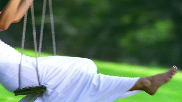 vidéos et rushes de close up tilt down tilt up pan woman in white dress swinging on tree swing outdoors - robe blanche