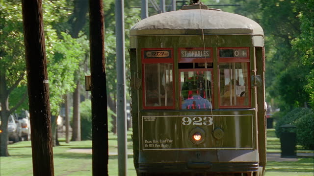 close up tilt down two st. charles avenue trolleys passing each other on tracks / new orleans, louisiana - tram stock videos & royalty-free footage