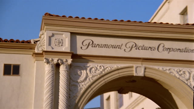1991 close up tilt down zoom out view of the Paramount Pictures studio gate / Los Angeles