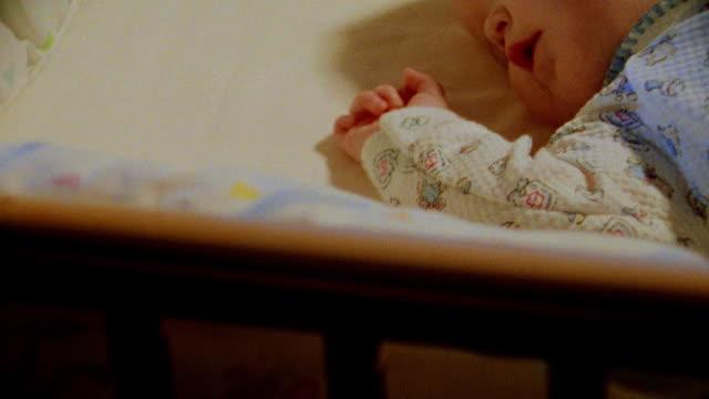 close up tilt up baby sleeping in crib in nursery