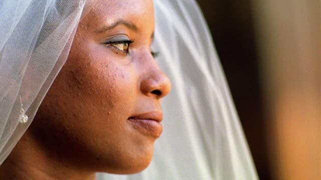 Close up tilt up Black bride turning head and smiling