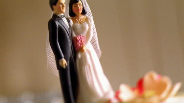 close up tilt up bride and groom cake decoration - figura maschile video stock e b–roll