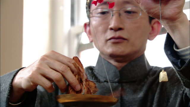 close up tilt up chinese herbalist placing handful of herbs on scale - chinese herbal medicine stock videos and b-roll footage