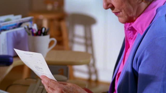 close up tilt up dolly shot pan from fax machine to senior woman sitting at computer paying bills + answering phone - コードレスフォン点の映像素材/bロール