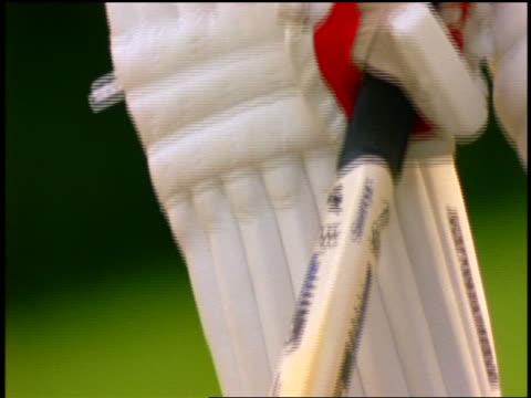 close up tilt up from bat to shinguards of batsman in cricket match / england - batsman stock videos & royalty-free footage