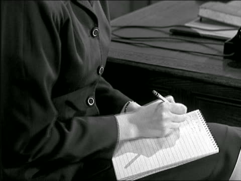 b/w 1947 close up tilt up from hands of secretary writing on notepad to her face wearing headphones - blocco per appunti video stock e b–roll