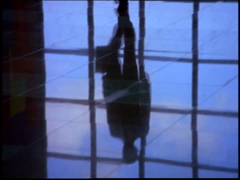 close up tilt up from reflection of businessman walking on shiny floor of building lobby to his legs / brazil - 書類鞄点の映像素材/bロール
