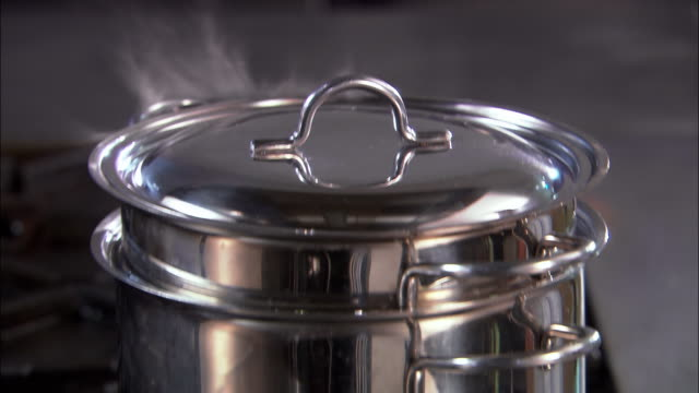 close up tilt up hands removing lid from double boiler on stove / adding spaghetti to boiling water / auckland - bollente video stock e b–roll