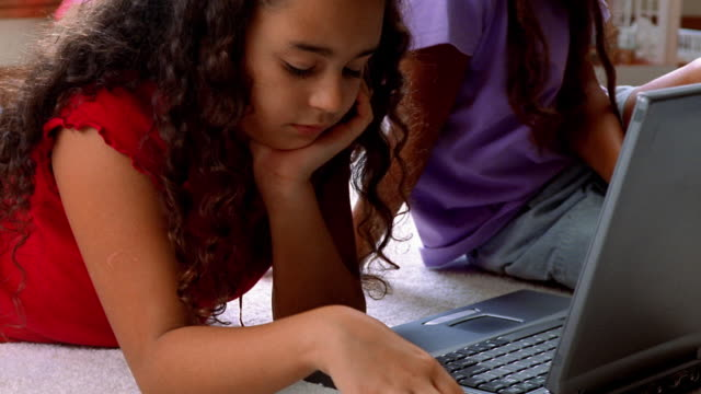 close up tilt up hispanic girl takes disc from other girl / inserts in laptop drive on floor - cd rom stock videos & royalty-free footage