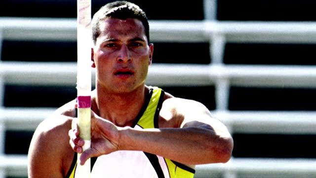 OVEREXPOSED SELECTIVE FOCUS close up tilt up Hispanic male pole vaulter lifts pole + starts to run toward cam