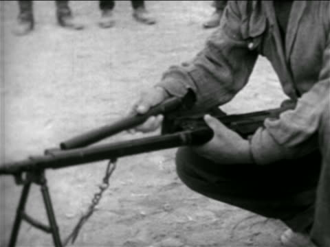 B/W 1957 close up tilt up kneeling man assembling rifle outdoors / Syria / newsreel