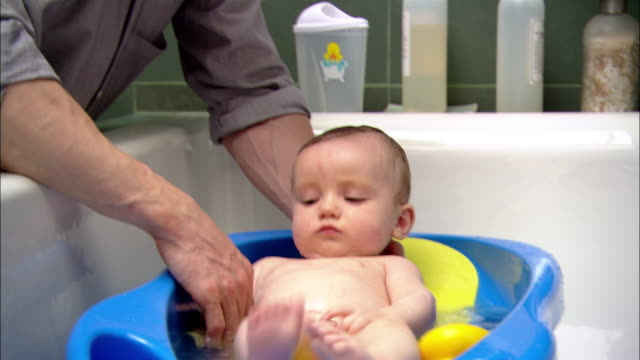 Close up tilt up man giving baby a bath / woman joining him at the tub