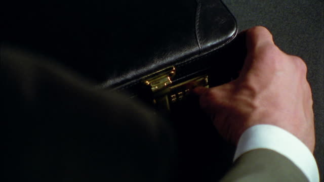 vídeos y material grabado en eventos de stock de close up tilt up man opening brief case full of cash - briefcase