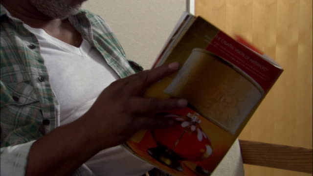 Close up tilt up man reading magazine/catalog in doctor's office waiting room / pan to nurse calling name and man walking through door