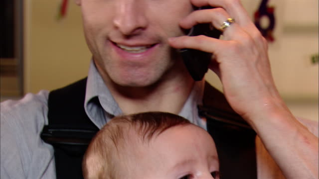 close up tilt up man talking on cell phone holding baby in carrier - multitasking bildbanksvideor och videomaterial från bakom kulisserna