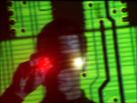 Close up tilt up man wearing specialized glasses and pointing red laser at circuit board projection