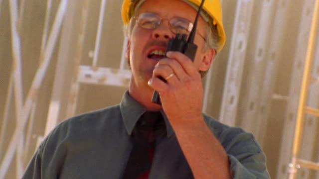 vídeos y material grabado en eventos de stock de close up tilt up man with hard hat + tie talking on walkie talkie + pointing off camera - walkie talkie