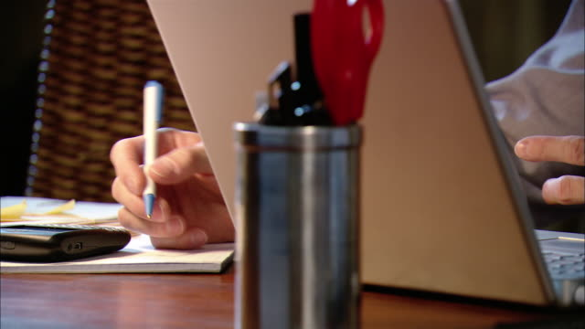 close up tilt up man writing on notepad in front of laptop computer at desk - in front of stock videos & royalty-free footage
