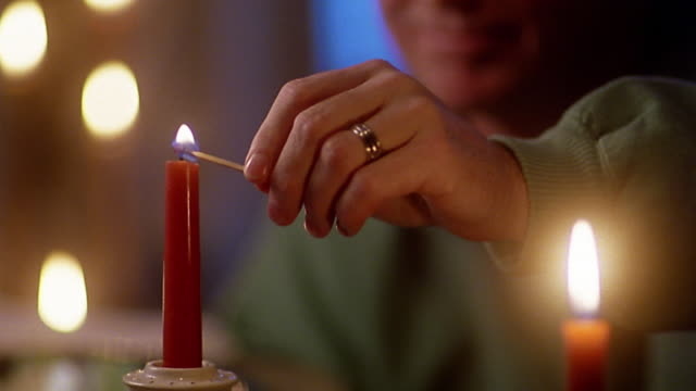 Close up tilt up man's hand lighting candle