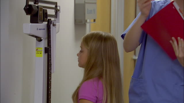 stockvideo's en b-roll-footage met close up tilt up nurse weighing young girl and measuring her height - lengte