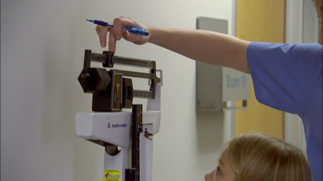 close up tilt up nurse weighing young girl and measuring her height - scales stock videos & royalty-free footage