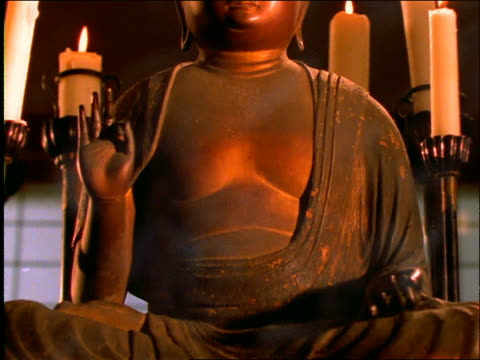 close up tilt up of amida buddha statue with candles / incense smoke in foreground - ローソク点の映像素材/bロール