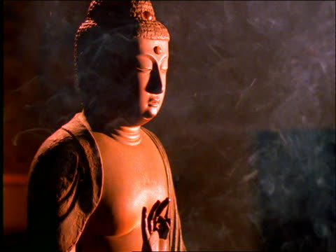 close up tilt up of amida buddha statue with incense smoke in foreground - männliche figur stock-videos und b-roll-filmmaterial