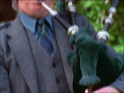 close up tilt up of man in grey suit playing bagpipes outdoors / birnam, scotland - perthshire stock videos & royalty-free footage