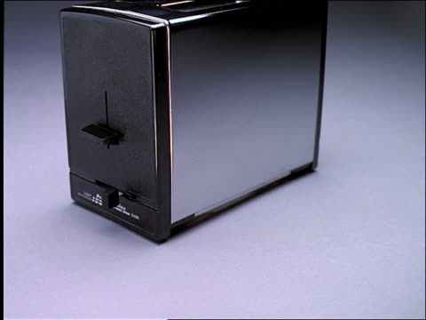 close up tilt up of toast popping up in toaster - toaster appliance stock videos & royalty-free footage
