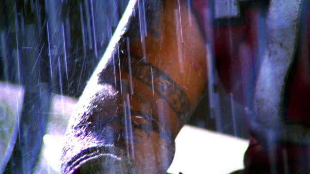 close up tilt up PORTRAIT Black football player sitting on bench in rain