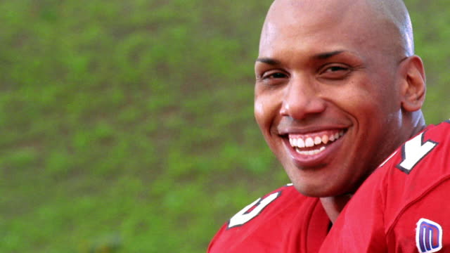 close up tilt up PORTRAIT Black football player smiling + laughing outdoors