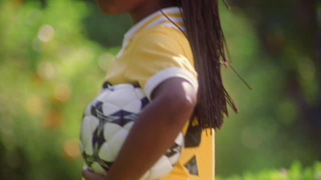 close up tilt up PORTRAIT Black girl holding soccer ball turning to camera smiling outdoors