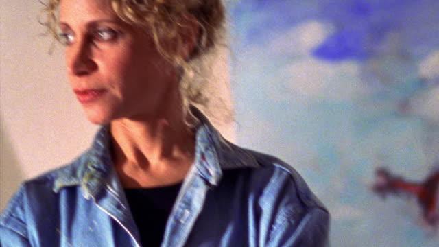 vídeos de stock e filmes b-roll de close up tilt up portrait blonde woman posing with artwork in background - só mulheres de idade mediana