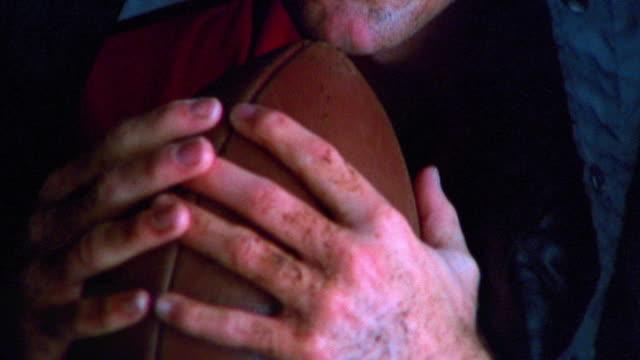 close up tilt up PORTRAIT football player holding ball