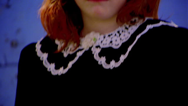 close up tilt up portrait from hands to face of redhead girl in black dress sitting outdoors looking somber - black dress stock videos & royalty-free footage