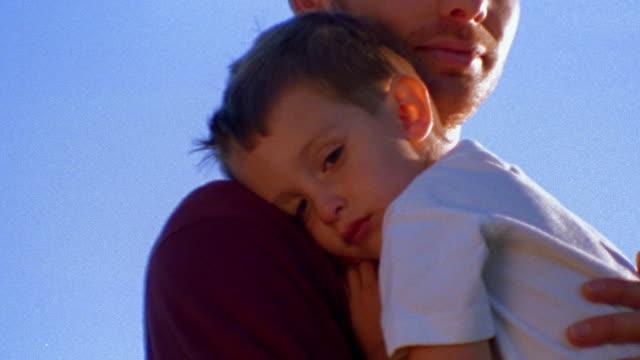 close up tilt up PORTRAIT man holding sleepy boy outdoors