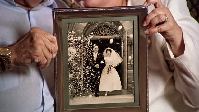 close up tilt up portrait senior couple sitting on sofa + holding archival photograph of their wedding day - couple relationship photos stock videos & royalty-free footage