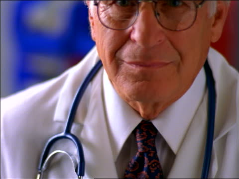 vídeos de stock, filmes e b-roll de close up tilt up portrait senior male doctor with stethoscope + eyeglasses smiling at camera - expressão facial