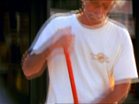 close up tilt up portrait white-haired man in t-shirt sweeping on sidewalk / he stops to look at camera / nyc - einzelner mann über 40 stock-videos und b-roll-filmmaterial