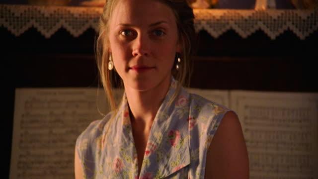 vídeos de stock e filmes b-roll de close up tilt up pan portrait young blonde woman sitting in front of upright piano - em frente de
