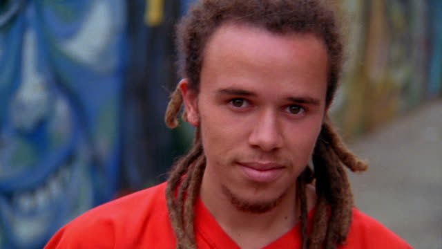 close up tilt up pan portrait young man with dreadlocks smiling next to murals of faces on wall / los angeles - mural stock videos & royalty-free footage