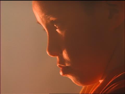 close up tilt up PROFILE Tibetan boy praying